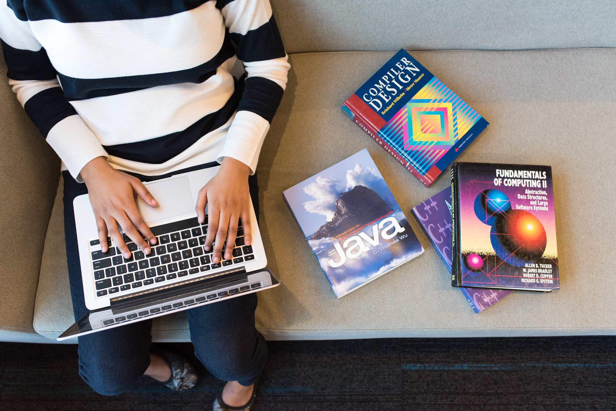 Woman working at a laptop with books