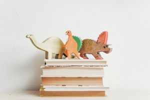 Toy dinosaurs on books
