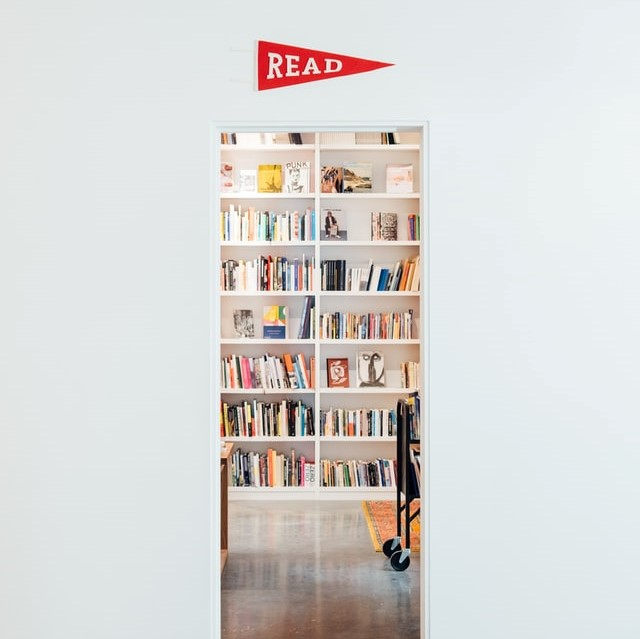 """A peak of a private, cozy, library from the view of a thin doorframe with a sign that says, """"read."""""""